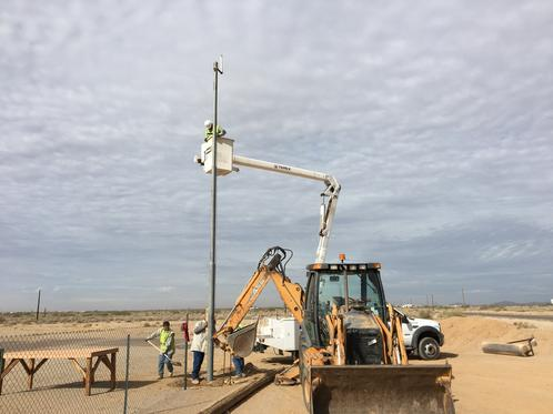 City Installing Pole For The Weather Station At Field